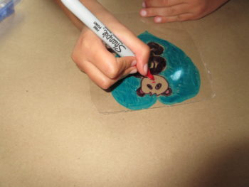 My daughter creating her own shrink art panda pendant.