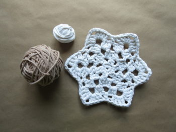 My crocheted snowflake trivet with a small ball of leftover, undyed t-shirt yarn, along with a full ball of t-shirt yarn I dyed using tea bags.